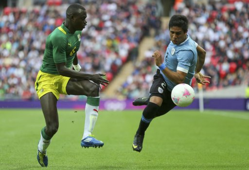 Senegal's Zargo Toure challenges Uruguay's Ramon Arias during their men's preliminary first round Group A soccer match at the London 2012 Olympic Games in the Wembley Stadium in London