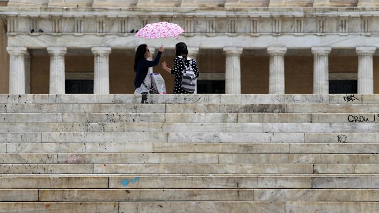 Tourists stand in front of the Greek Parliament during a rainfall in Athens, Friday, May 18, 2012. Greece's Parliament is to be dissolved so new elections can be held June 17. The move Friday comes after an inconclusive election left squabbling politicians unable to form government, deepening the country's political crisis and jeopardizing its membership in Europe's joint currency. (AP Photo/Thanassis Stavrakis)