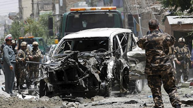 Afghan security forces stand at the site of a suicide attack in Kabul, Afghanistan
