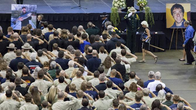 Attendees salute as a family member of the deceased exits at the end of a memorial for U.S. Forest Service firefighters  Zbyszewski,  Zajac, and Wheeler, who died fighting the Okanogan Comp