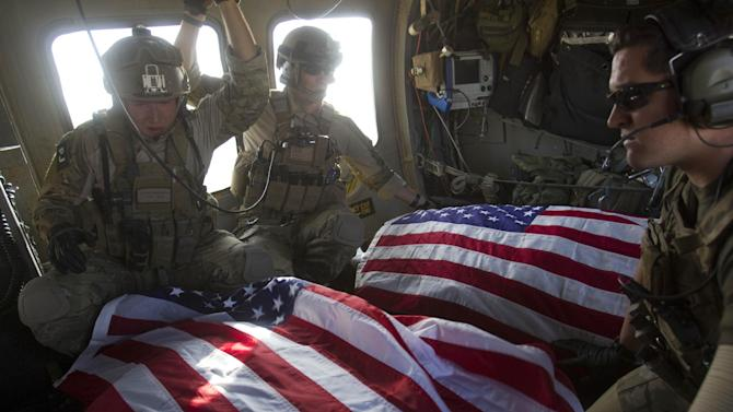 FILE - U.S. Air Force pararescuemen ride in the back of their medivac helicopter with the American flag draped over bodies of U.S. soldiers who were killed in a roadside bomb attack in Afghanistan's Kandahar province on Oct. 10, 2010. (AP Photo/David Guttenfelder, File)