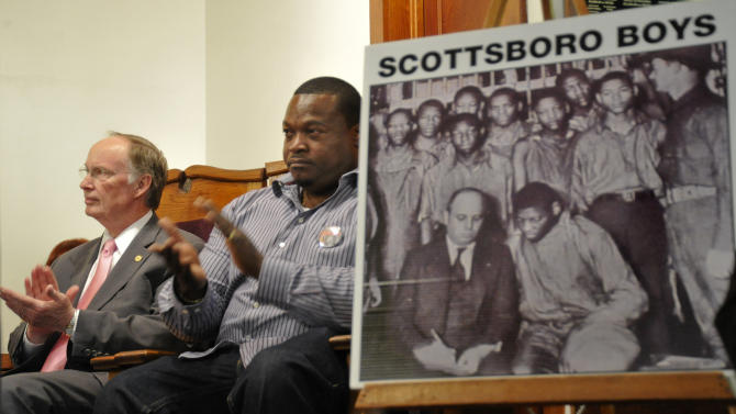 FILE - In this file photo taken April 19, 2013, Alabama Gov. Robert Bentley, left, and Clarence Norris Jr. applaud during a ceremony in Scottsboro, Ala. They are seated next to a photo of the Scottsboro Boys, the nine African American youths wrongfully convicted of raping two Caucasian women more than 80 years ago, in Scottsboro, Ala. Now that the Alabama Legislature is allowing posthumous pardons for the Scottsboro Boys, there is still much work to be done before their names are officially cleared. (AP Photo/al.com, Bob Gathany, file)