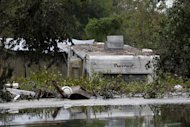 A building and camper are inundated in floodwaters from Hurricane Isaac in Braithwaite, La., Sunday, Sept. 2, 2012. More than 200,000 people across Louisiana still didn't have any power five days after Hurricane Isaac ravaged the state. Thousands of evacuees remained at shelters or bunked with friends or relatives. (AP Photo/Gerald Herbert)