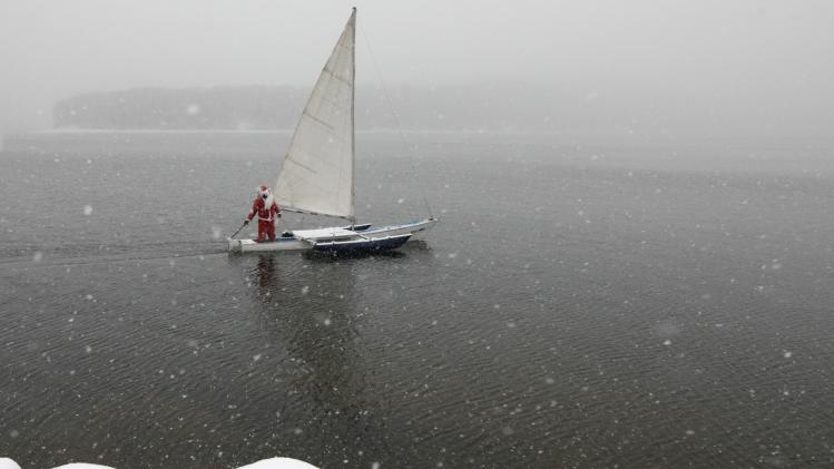"A member of the ""Skipper"" yacht club dressed as Santa Claus, sails his trimaran to mark the ending of the sailboat season during heavy snowfall outside Krasnoyarsk"
