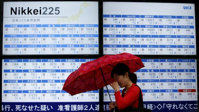 Woman holding an umbrella walks past an electronic board showing Japan's Nikkei 225 outside a brokerage in Tokyo