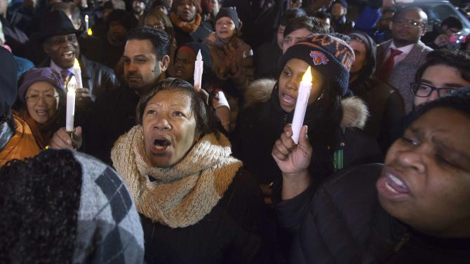 People sing as they take part in prayer vigil at site where two police officers were shot in Brooklyn borough of New York