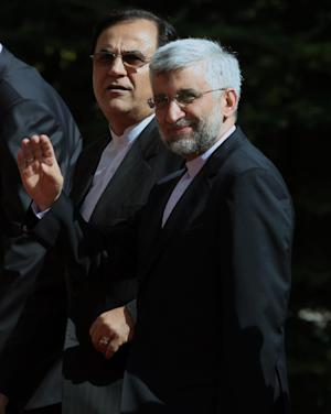 """Iran's chief nuclear negotiator Saeed Jalili, right, waves as he arrives for a meeting with Turkish Prime Minister Recep Tayyip Erdogan in Ankara, Turkey, Tuesday, Sept. 18, 2012. Iran on Tuesday urged Western powers to engage in """"purposeful"""" negotiations as top EU and Iranian representatives prepared to meet for talks on restarting stalled negotiations over Tehran's nuclear program. The EU's Foreign policy Chief Catherine Ashton and Jalili are meeting in Istanbul later on Tuesday. (AP Photo/Burhan Ozbilici, Pool)"""