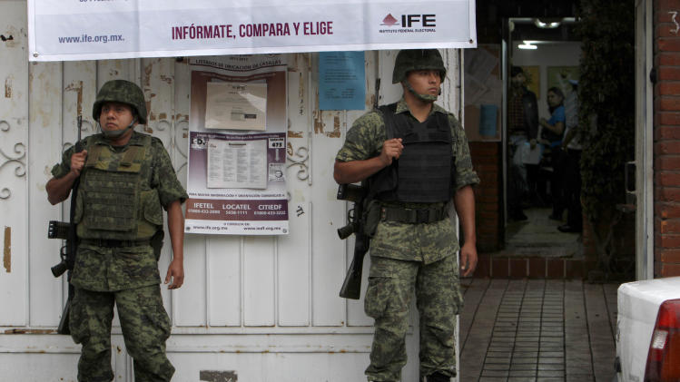 Soldiers stand guard outside an office of the Federal Electoral Institute (IFE) ahead of elections in Mexico City, Saturday, June 30, 2012. Mexico will hold general elections, including the presidential election, on July 1. (AP Photo/Marco Ugarte)