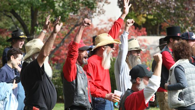 In this Saturday, Oct. 28, 2012, photo, Virginia City residents celebrate winning the most bearded community award during the Nevada Day beard contest at the amphitheaters south of the Nevada State Capitol in Carson City, Nev. (AP Photo/Nevada Appeal, Jim Grant)