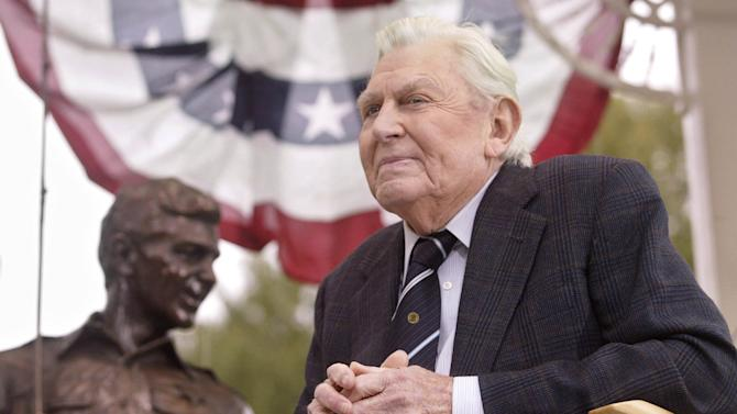 """FILE - This Oct. 28, 2003 file photo shows actor Andy Griffith sitting in front of a bronze statue of Andy and Opie from the """"Andy Griffith Show,"""" after the unveiling ceremony in Raleigh, N.C.  Griffith, whose homespun mix of humor and wisdom made """"The Andy Griffith Show"""" an enduring TV favorite, died Tuesday, July 3, 2012 in Manteo, N.C. He was 86. (AP Photo/Bob Jordan, File)"""