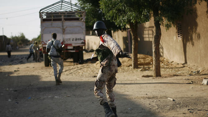 A Malian soldier motions to take cover during exchanges of fire with jihadists in Gao, northern Mali, Sunday, Feb. 10, 2013. (AP Photo/Jerome Delay)