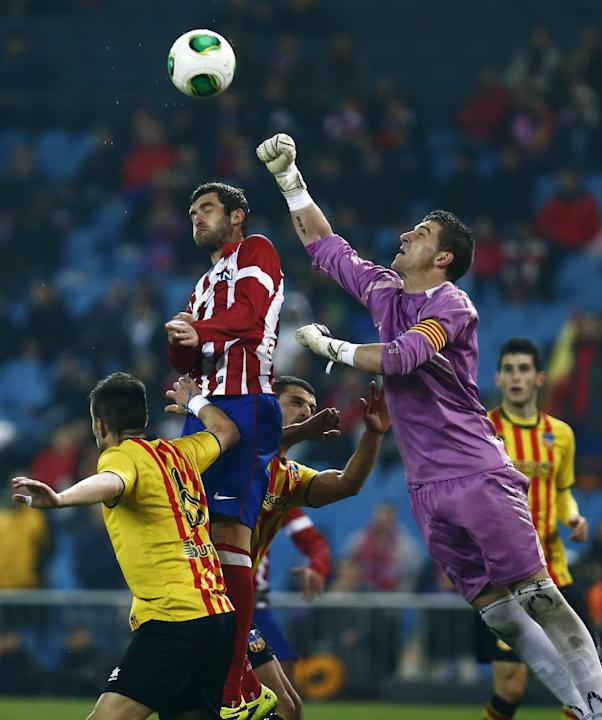 Sant Andreu's goalkeeper Pau Nunez, top right, in action with Atletico's Leo Baptistao, top left, during a Copa del Rey soccer match between Atletico de Madrid and Sant Andreu at the Vicente C