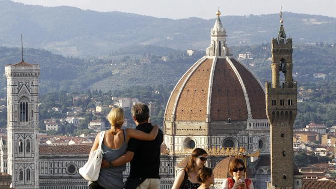 "FILE - In this July 8, 2013 file photo, a couple looks at the Florence Santa Maria del Fiore Basilica, with Giotto's bell tower, left, Brunelleschi's dome, from Forte Belvedere, Italy. ""When they get to these more dramatic occasions, so many couples want to do something exciting and different,"" says Charles Schmitz of St. Louis. He and his wife, Elizabeth, are marriage counselors and authors, most recently of ""How to Marry the Right Guy'' (Briarcliff, 2014). (AP Photo/Francesco Bellini, File)"