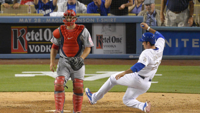 Los Angeles Dodgers' Adrian Gonzalez, right, scores on a single by Jerry Hairston Jr. as Los Angeles Angels catcher Hank Conger looks on during the seventh inning of their baseball game, Monday, May 27, 2013, in Los Angeles.  (AP Photo/Mark J. Terrill)