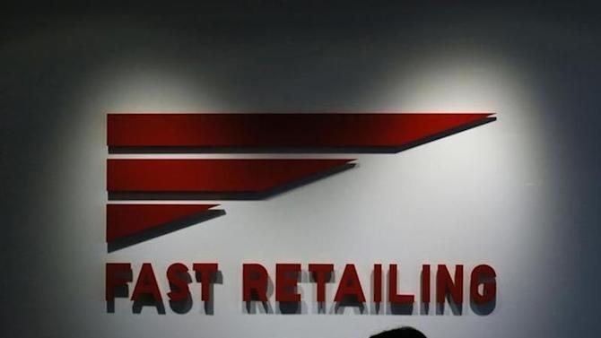 An employee of Fast Retailing Co is silhouetted in front of its logo at its headquarters in Tokyo