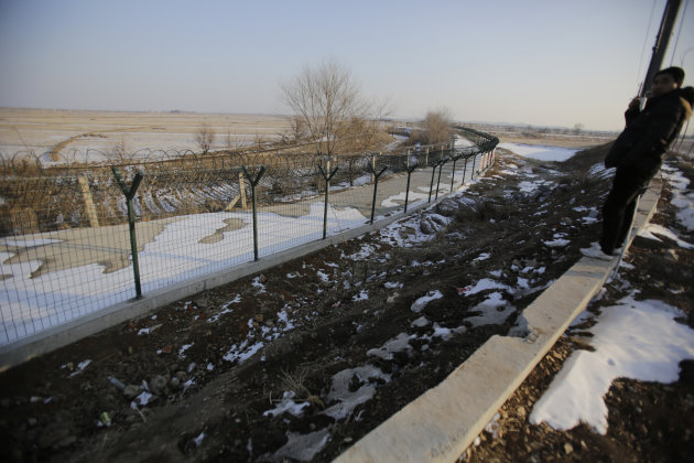 In this Feb. 6, 2013 photo, a Chinese tourist looks at a newly erected border fence in Dandong, China, opposite the North Korean border town of Sinuiju. China's patience with North Korea is wearing th