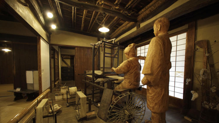 In this photo taken Monday, Feb. 18, 2013, a wooden hand loom with models of a boy and a woman, portraying Sakichi Toyoda and his mother, is displayed inside the renovated house where Sakichi Toyoda, father of Toyota Motor Corp. founder Kiichiro Toyoda and great-grandfather of current President Akio Toyoda, was born in Kosai, central Japan. Sakichi Toyoda invented an automatic loom in a backyard shed, mainly because he wanted to help his mother, who often was weaving in their home. Those around him, including his carpenter father, thought he was crazy and laughed at him. When Kiichiro Toyoda wanted to develop cars in 1933, not just keep making the by-then successful looms, people again laughed. Back then, Japan only had imported cars like GMs and Fords. (AP Photo/Shizuo Kambayashi)