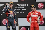 Red Bull-Renault driver Sebastian Vettel of Germany (left) celebrates his victory on the podium next to third-placed Ferrari driver Fernando Alonso of Spain after winning the Formula One Korean Grand Prix at the Korean Circuit in Yeongam on October 14, 2012