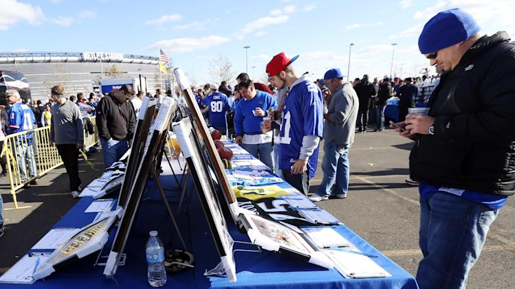 Fans look at items in a silent auction being held to raise money for people suffering from the affects of Superstorm Sandy and cystic fibrosis before an NFL football game between the New York Giants and the Pittsburgh Steelers, Sunday, Nov. 4, 2012, in East Rutherford, N.J. (AP Photo/Julio Cortez)