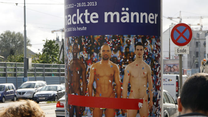 "FILE - In this Oct. 18, 2012 file photo two people walk past a poster showing three naked men which has had red tape added to cover the sensitive parts of the three men, in Vienna, Austria. Poster reads: ""Naked Men"". A prestigious Vienna museum, The Leopold Museum, says a man took the concept of life imitating art to an extreme recently when he suddenly stripped at an exhibition of pictures and sculptures portraying nude men through the ages. A museum spokesman said Tuesday Dec. 11, 2012 that after taking his clothes off, the man calmly sauntered through the exhibition, dressing again only after a security guard asked him to do so. (AP Photo/Ronald Zak, File)"