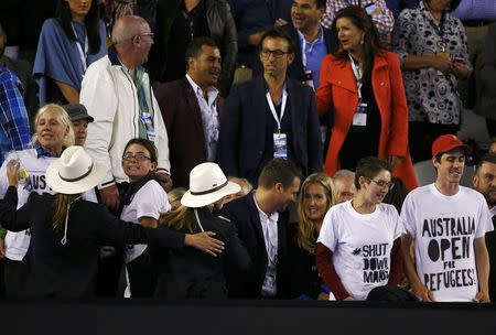 Protesters display slogans on their t-shirts during the men's singles final match between Djokovic of Serbia and Murray of Britain at the Australian Open 2015 tennis tournament in Melbourne