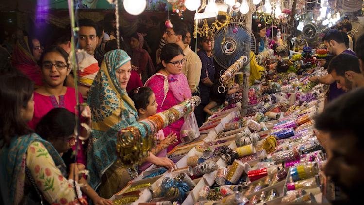 Pakistani customers buy bangles ahead of the Muslim holiday of Eid al-Fitr in Islamabad, Pakistan, Monday, July 28, 2014. Pakistani Muslims will celebrate the Eid al-Fitr holiday that marks the end of the holy fasting month of Ramadan. (B.K. Bangash)