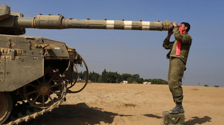 An Israeli soldier checks a tank near the border with Gaza