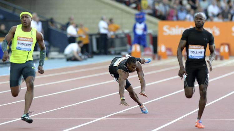 Yohan Blake falls onto the track during the men's 100m on day one of the Diamond League Meeting at Hampden Park, Glasgow. Friday July 11, 2014. (AP Photo/PA, Martin Rickett) UNITED KINGDOM OUT NO SALES NO ARCHIVE
