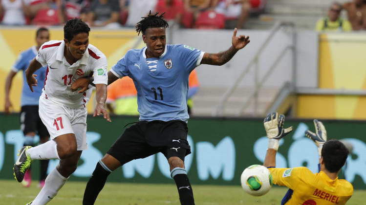 Challenged by Tahiti's Jonathan Tehau, left, Uruguay's Abel Hernandez scores past goalkeeper Gilbert Meriel during a soccer Confederations Cup group B match at the Arena Pernambuco in Recife, Brazil, Sunday, June 23, 2013. (AP Photo/Eugene Hoshiko)
