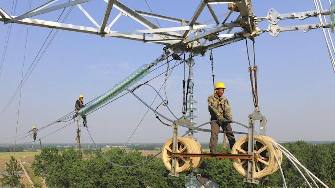 Workers install wires on an electricity pylon in Chuzhou