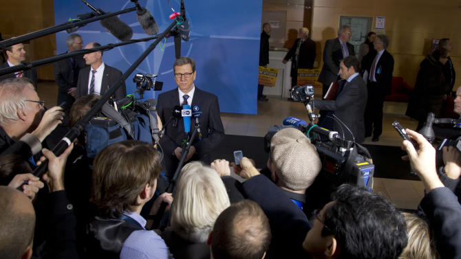 German Foreign Minister Guido Westerwelle, center rear, speaks with the media as he arrives for a meeting of NATO foreign ministers at NATO headquarters in Brussels on Tuesday, Dec. 4, 2012. NATO foreign ministers are expected to approve Turkey's request for Patriot anti-missile systems to bolster its defense against possible strikes from neighboring Syria. (AP Photo/Virginia Mayo)
