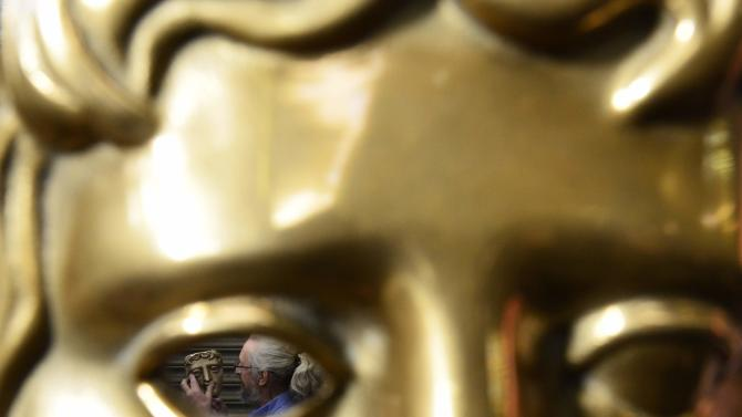 Patrick Helly, managing director of New Pro Foundry is seen through an eye of a bronze BAFTA mask as he poses with partially finished mask at foundry in west London
