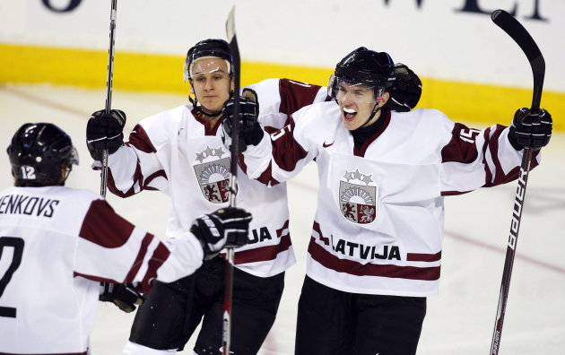 File - Team Latvia's Juris Ziemins, right, celebrates his goal with teammates Vitalijs Hvorostinins, centre, and Arturs Kuzmenkovs during second period IIHF World Junior Championships hockey action against Team Slovakia in Calgary, Alta., Tuesday, Dec. 27, 2011.THE CANADIAN PRESS/Jeff McIntosh