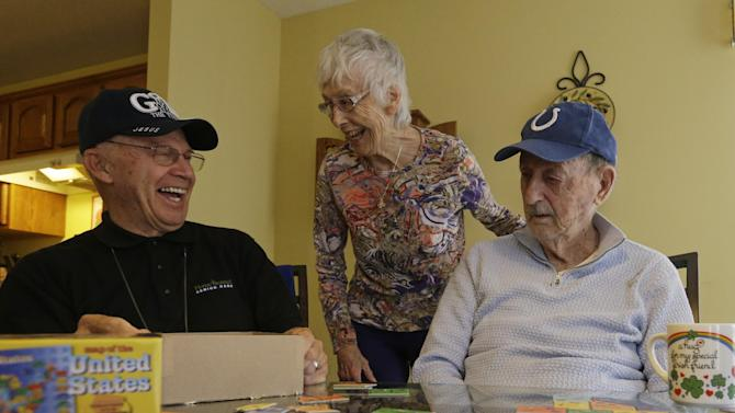 In this Nov. 21, 2013 photo, caregiver Warren Manchess, left, laughs with Paul Gregoline and Paul's wife, Mary, as they work on a puzzle, in Noblesville Ind. Burgeoning demand for senior services like home health aides is being met by a surprising segment of the workforce: Other seniors. Twenty-nine percent of so-called direct-care workers are projected to be 55 or older by 2018 and in some segments of that population older workers are the single largest age demographic. With high rates of turnover, home care agencies have shown a willingness to hire older people new to the field who have found a tough job market as they try to supplement their retirement income.(AP Photo/Darron Cummings)
