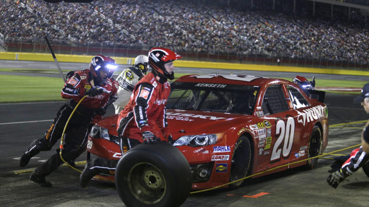 Crew members perform a pit stop on driver Matt Kenseth's car during the NASCAR Sprint Cup series Coca-Cola 600 auto race at Charlotte Motor Speedway in Concord, N.C., Sunday, May 26, 2013. (AP Photo/Nell Redmond)