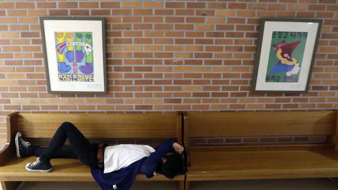 """In this picture taken on Wednesday, May 29, 2013, an unidentified North Korean defector takes a nap near the paintings wishing two Koreas reunification during a break time at the Hangyeore middle-high school in Anseong, south of Seoul, South Korea. North Korea's prison population has swelled in recent years with those caught fleeing the country under a crackdown on defections by young leader Kim Jong Un, according to defectors living in South Korea and researchers who study Pyongyang's notorious network of labor camps and detention centers. The letters read """"Reunification and A journey of thousand miles begins with one step."""" (AP Photo/Lee Jin-man)"""
