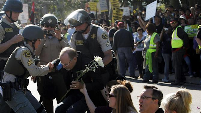 Demonstrators are arrested by police after protesting outside a Walmart store Friday Nov. 23, 2012, in Paramount, Calif.  Wal-Mart employees and union supporters are taking part in today's nationwide demonstration for better pay and benefits A union-backed group called OUR Walmart, which includes former and current workers, was staging the demonstrations and walkouts at hundreds of stores on Black Friday, the day when retailers traditionally turn a profit for the year.    (AP Photo/Nick Ut)
