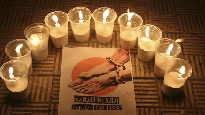 Lit candles are placed by activists around a placard during a vigil in solidarity with the detainees in Syrian prisons at Aleppo's Salaheddine neighborhood