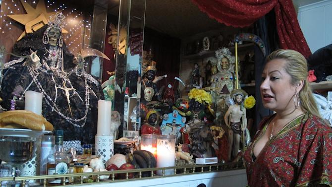In this Feb. 12, 2013 photo, Arely Vazquez Gonzalez, a Mexican immigrant and transgender woman, is shown with her alter to La Sante Muerte at her Queens, NY apartment.  La Santa Muerte, an underworld saint most recently associated with the violent drug trade in Mexico, now is spreading throughout the U.S. among a new group of followers ranging from immigrant small business owners to artists and gay activists.  (AP Photo/Russell Contreras)