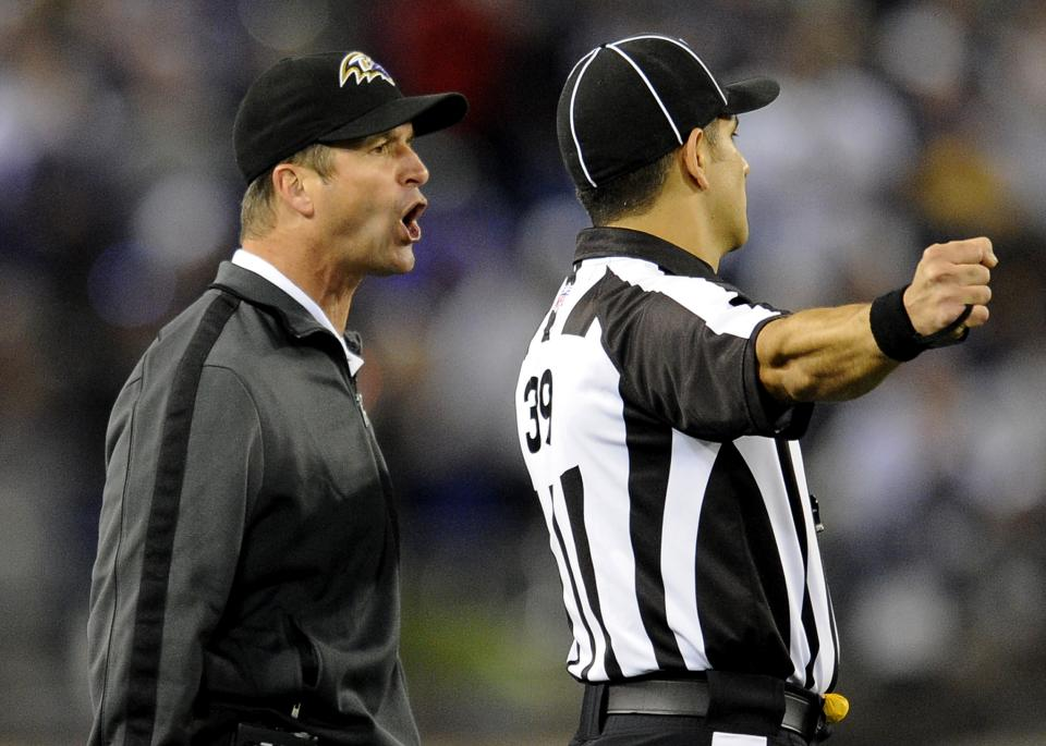 Baltimore Ravens head coach John Harbaugh, left, talks with line judge Esteban Garza during the first half of an NFL football game against the New England Patriots in Baltimore, Sunday, Sept. 23, 2012. (AP Photo/Nick Wass)