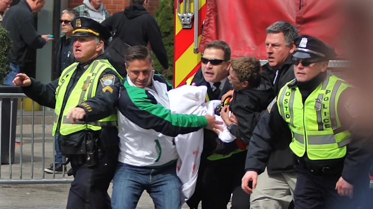 In this Monday, April 15, 2013, photo, emergency personnel carry a wounded person away from the scene of an explosion at the 2013 Boston Marathon in Boston. Two explosions shattered the euphoria of the Boston Marathon finish line on Monday, sending authorities out on the course to carry off the injured while the stragglers were rerouted away from the smoking site of the blasts. People across the country echoed strains of defiance, tenderness and wariness as Americans try to make sense of Boston bombings. (AP Photo/Kenshin Okubo)