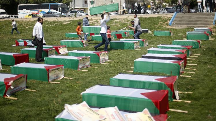 Palestinians look at mock coffins symbolising Palestinian prisoners who died in Israeli jails, on the Palestinian Prisoner Day, in Gaza City
