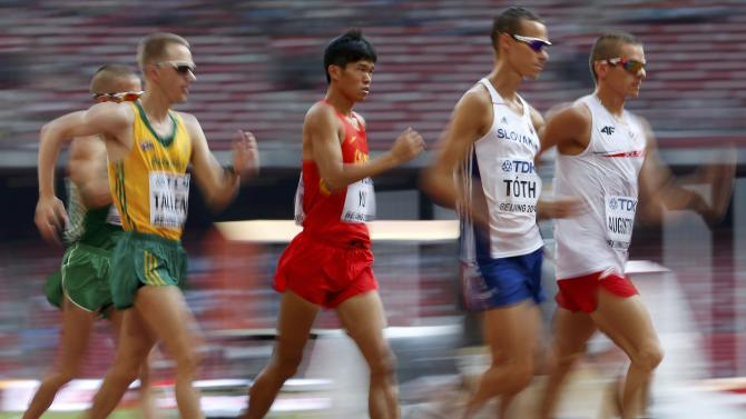 Rafal Augustyn of Poland (R) leads the pack as he competes at the start of the men's 50 km race walk final during the 15th IAAF World Championships at the National Stadium in Beijing