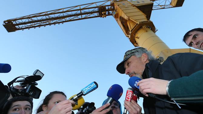 """French father Serge Charnay answers journalists after he climbed down from  the crane where he was spending the fourth day in protest, Monday, Feb,18, 2013. The man, wants France to strengthen its law on shared custody. He was convicted of taking his son on an unauthorized vacation for two months in 2011, and said he regretted nothing because """"if I hadn't I wouldn't have seen him."""" (AP Photo/David Vincent)"""