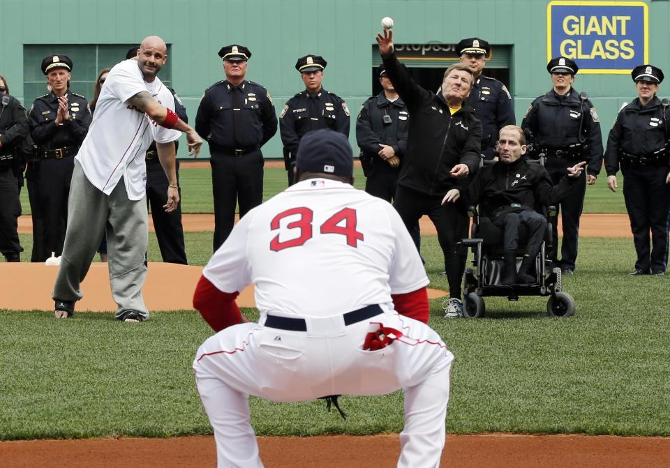 Boston Marathon bombing victim Steven Byrne, midground left, and marathon runners Dick and Rick Hoyt, midground right, throw out ceremonial first pitches as Boston Red Sox's David Ortiz  (34) catches before a baseball game against the Kansas City Royals in Boston, Saturday, April 20, 2013. (AP Photo/Michael Dwyer)