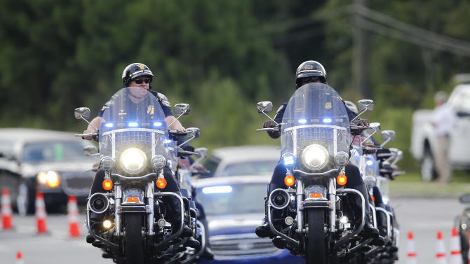 Police officers on motorcycles led a procession of mourners to a funeral for Bobbi Kristina Brown Saturday, Aug. 1, 2015, in Alpharetta, Ga.  Brown, the only child of Whitney Houston and R&B singer Bobby Brown, died in hospice care July 26, about six months after she was found face-down and unresponsive in a bathtub in her suburban Atlanta townhome. (AP Photo/John Bazemore)