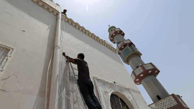 Workers install a security camera at the Al A'ali Grand Mosque, ahead of Friday prayers in Al A'ali south of Manama
