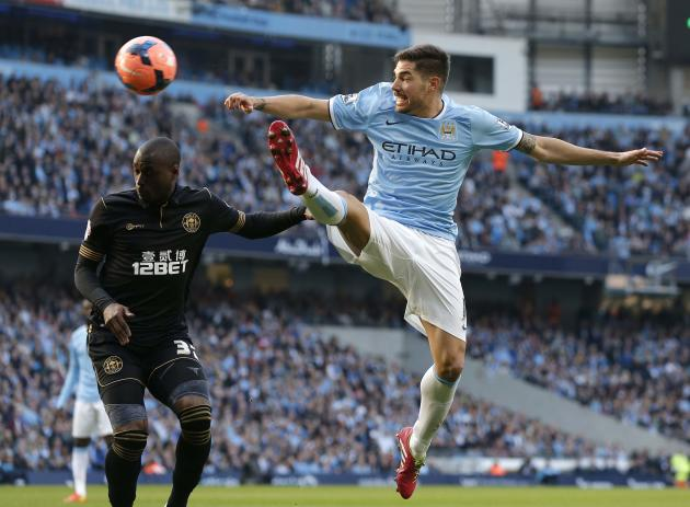 Wigan Athletic's Fortune challenges Manchester City's Garcia during their English FA Cup quarter final soccer match at the Etihad stadium in Manchester