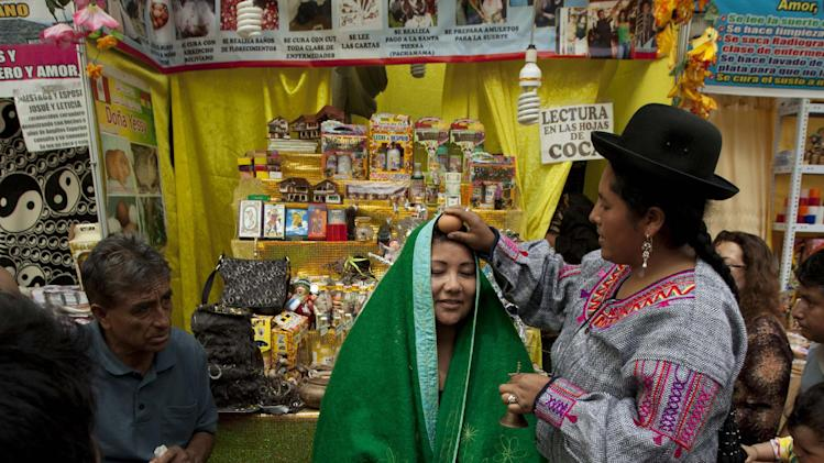 Shaman Yessy, right, performs a New Year's ritual to bring good luck to her client in the coming year, at the Market of Wishes in Lima, Peru, Monday, Dec. 31, 2012. (AP Photo/Martin Mejia)