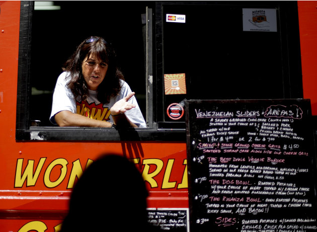 Wendy Cross talks to a customer from her food truck Tuesday, July 10, 2012, in Atlanta. After penning a rambling confession to financial regulators and writing notes to his family, a south Georgia ban